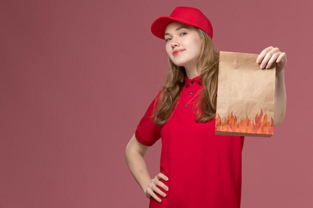 Vrouwelijke koerier in rood uniform die voedselpapierpakket op roze, uniforme dienstbezorgingswerker houdt