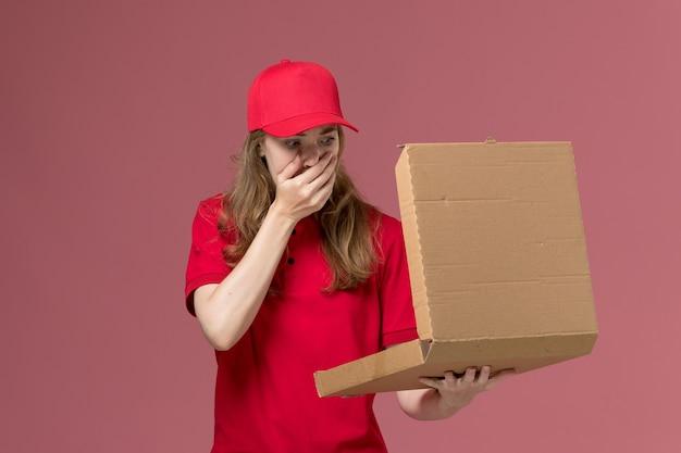 Vrouwelijke koerier in rood uniform houden en openen van voedseldoos op lichtroze, baan uniforme dienstverlener levering