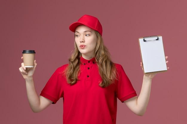 Vrouwelijke koerier in rood uniform met bruine bezorging koffiekopje en blocnote op roze, uniforme dienstverlener