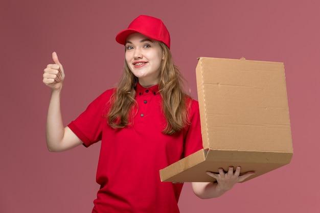 Vrouwelijke koerier in rood uniform met bruine levering voedsel doos glimlachend op lichtroze, uniform baan service werknemer levering meisje