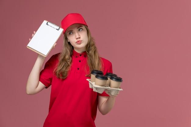 Vrouwelijke koerier in rood uniform met koffiekopjes en blocnote op roze, uniforme dienstverlener