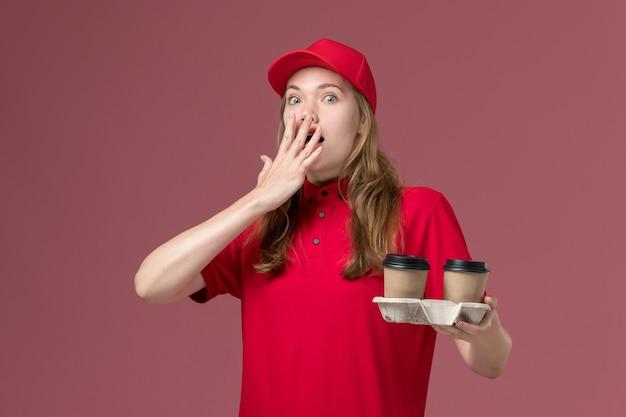Vrouwelijke koerier in rood uniform met koffiekopjes met verbaasde uitdrukking op roze, uniforme dienstverlening
