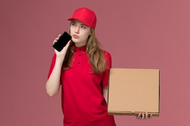 Vrouwelijke koerier in rood uniform met telefoonvoedselbox op lichtroze, baan uniforme dienstverlener levering