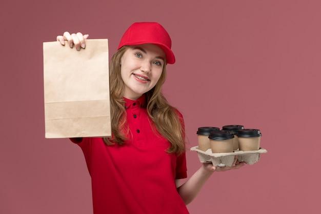 Vrouwelijke koerier in rood uniform met voedselpakket en koffiekopjes op lichtroze, baanuniforme servicemedewerker levering