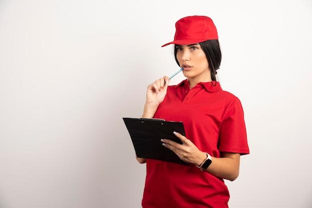 Vrouwelijke koerier in rood uniform na te denken over iets. hoge kwaliteit foto