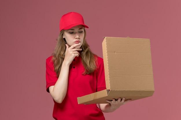 Vrouwelijke koerier in rood uniform vasthouden en openen van leveringsdoos op lichtroze, baan uniforme servicemedewerker levering