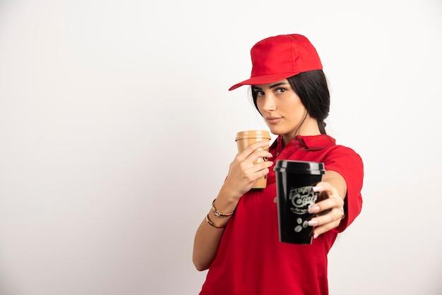 Vrouwelijke koerier in rood uniform weggeven van een kopje koffie. hoge kwaliteit foto