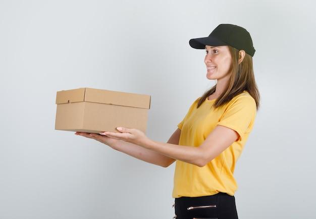 Vrouwelijke koerier levert kartonnen doos in t-shirt, broek en pet