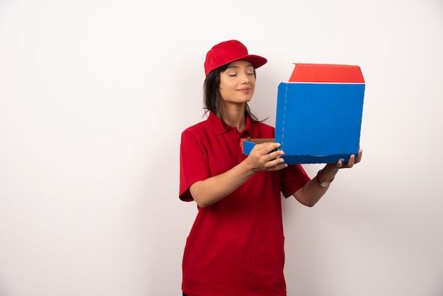 Vrouwelijke koerier met gesloten ogen die een doos pizza vasthoudt