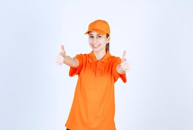 Vrouwelijke koerier met oranje uniform en pet met duim omhoog