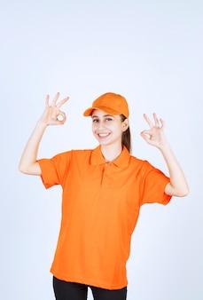 Vrouwelijke koerier met oranje uniform en pet met ok handteken