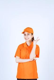 Vrouwelijke koerier met oranje uniform en pet met vredesteken