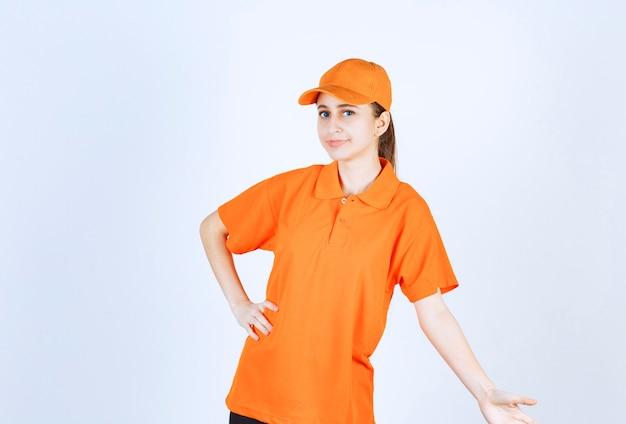 Vrouwelijke koerier met oranje uniform en pet.