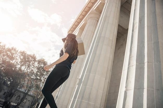 Vrouwelijke koerier met perceel lopen in de buurt van betonnen kolom