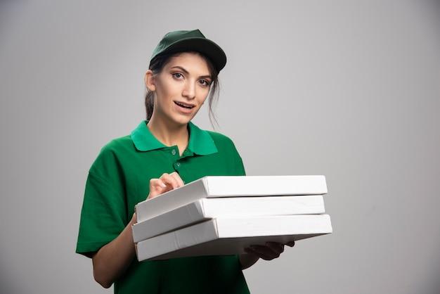 Vrouwelijke koerier poseren met pizzadozen