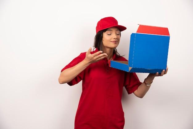 Vrouwelijke koerier snuffelt aan doos pizza