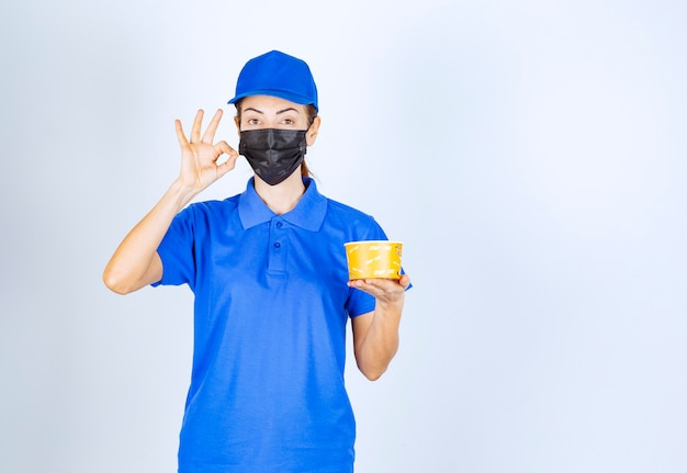 Vrouwelijke koerier van het restaurant in blauw uniform en gezichtsmasker die een afhaalmaaltijd levert en de goede smaak garandeert.