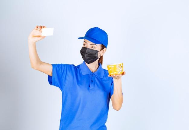 Vrouwelijke koerier van het restaurant in blauw uniform en gezichtsmasker die een afhaalmaaltijd levert en haar visitekaartje presenteert.