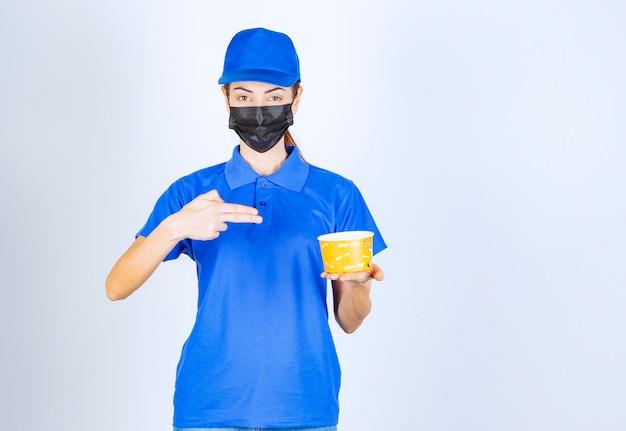Vrouwelijke koerier van het restaurant in blauw uniform en gezichtsmasker met een afhaalmaaltijd.