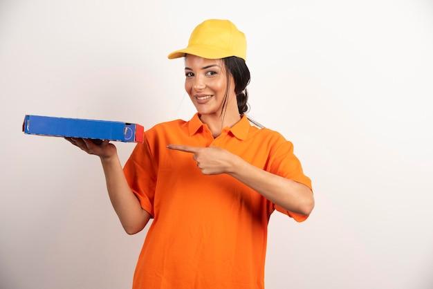 Vrouwelijke koerier wijzend op karton van pizza.