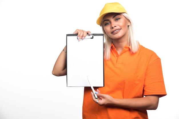 Vrouwelijke koerier wijzend op leeg notitieboekje op witte achtergrond. hoge kwaliteit foto