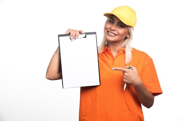 Vrouwelijke koerier wijzend op lege notebook terwijl pen op witte achtergrond. hoge kwaliteit foto