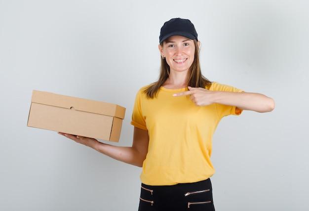 Vrouwelijke koerier wijzende vinger op kartonnen doos in t-shirt, broek, pet en op zoek blij