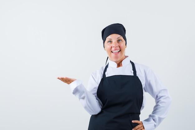 Vrouwelijke kok die doet alsof ze iets in uniform, schort vasthoudt en er blij uitziet. vooraanzicht.