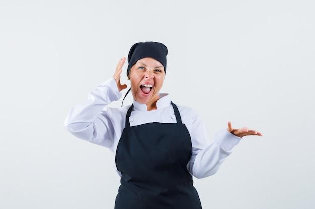 Vrouwelijke kok die doet alsof ze iets in uniform, schort vasthoudt en er gelukkig uitziet, vooraanzicht.
