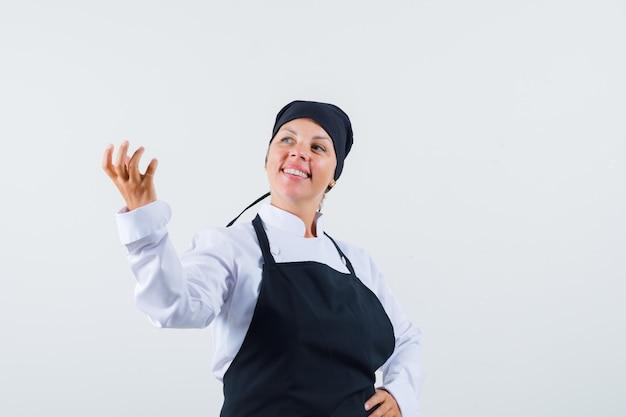 Vrouwelijke kok die doet alsof ze iets vasthoudt in uniform, schort en er vrolijk uitziet. vooraanzicht.