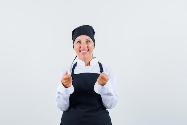 Vrouwelijke kok die doet alsof ze iets vasthoudt in uniform, schort en optimistisch kijkt. vooraanzicht.