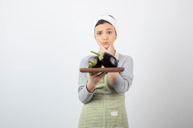 Vrouwelijke kok die een bord met grote aubergines vasthoudt en denkt.