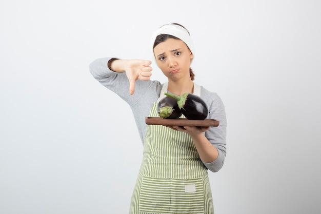Vrouwelijke kok die een bord met grote aubergines vasthoudt en duimen naar beneden geeft.