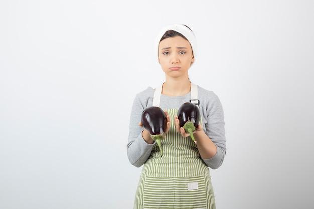 Vrouwelijke kok die grote aubergines op wit houdt.