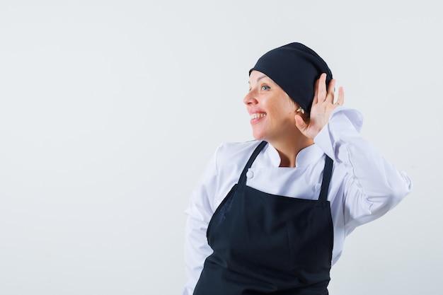 Vrouwelijke kok die hand dichtbij oor in uniform, schort houdt en nieuwsgierig, vooraanzicht kijkt.