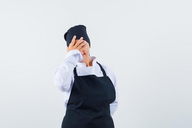 Vrouwelijke kok die hand op gezicht in uniform, schort houdt en gelukkig kijkt. vooraanzicht.