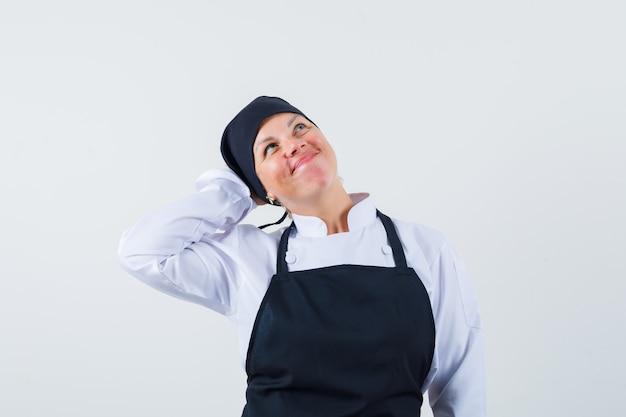 Vrouwelijke kok die hand op hoofd in uniform, schort houdt en er dromerig uitziet. vooraanzicht.