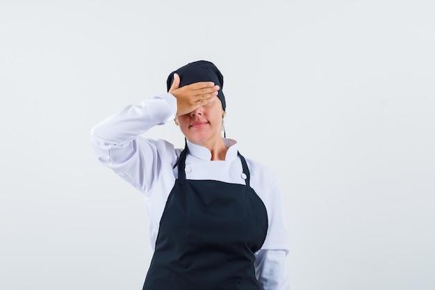 Vrouwelijke kok die hand op ogen in uniform, schort houdt en beschaamd kijkt, vooraanzicht.