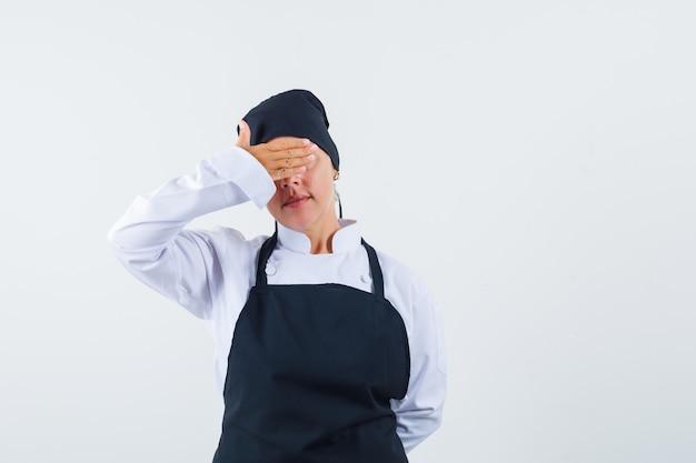 Vrouwelijke kok die hand op ogen in uniform, schort houdt en kalm, vooraanzicht kijkt.