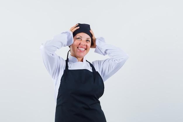 Vrouwelijke kok die handen op hoofd in uniform, schort houdt en vreugdevol, vooraanzicht kijkt.
