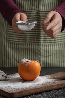 Vrouwelijke kok die meel morst op zoete persimmon in de keuken