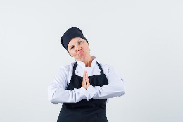 Vrouwelijke kok die namaste-gebaar in uniform, schort toont en aarzelend, vooraanzicht kijkt.