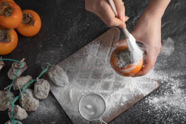 Vrouwelijke kok die persimmon decoreert met bloem op zwarte ondergrond