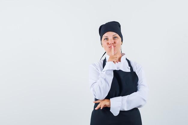 Vrouwelijke kok die stiltegebaar in uniform, schort toont en er verstandig uitziet. vooraanzicht.