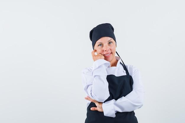 Vrouwelijke kok die zich in het denken bevindt stelt in uniform, schort en ziet er verstandig uit. vooraanzicht.