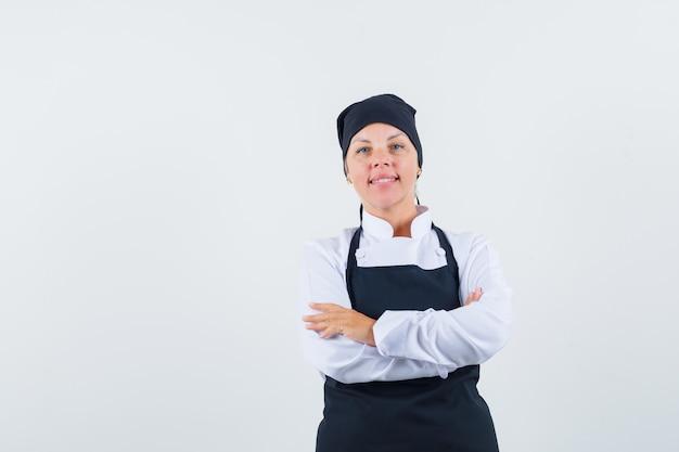 Vrouwelijke kok die zich met gekruiste armen in uniform, schort bevindt en er zelfverzekerd uitziet. vooraanzicht.