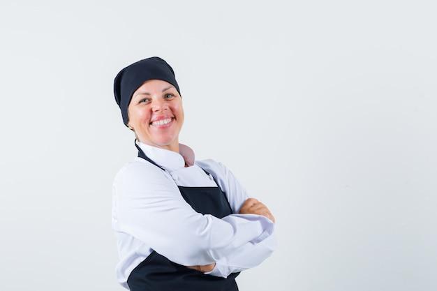 Vrouwelijke kok die zich met gekruiste armen in uniform, schort bevindt en gelukkig, vooraanzicht kijkt.