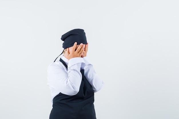 Vrouwelijke kok hand in hand op gezicht in uniform, schort en depressief op zoek. vooraanzicht.