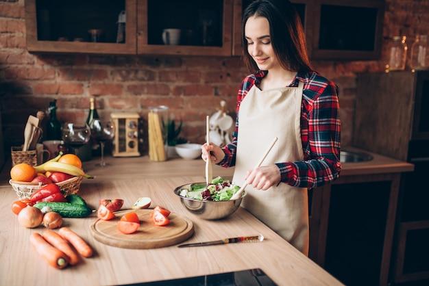Vrouwelijke kok houdt houten lepel, groentesalade koken in de keuken. bereiding van verse dieetvoeding. vrouw bereidt een romantisch diner voor haar man