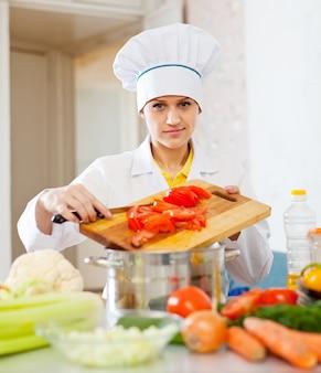 Vrouwelijke kok in toque werken op commerciële keuken